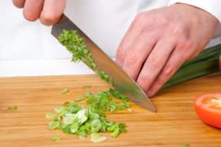Chef slicing scallions on wooden cutting board