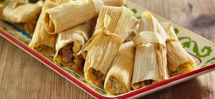 overflowing platter of tamales, wrapped in corn husks