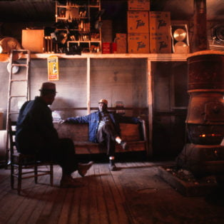 Winter, Chulahoma, Miss. Morris Shaw and Elvan Clark around the stove in Waldrip's General Store. 1973 Photography 13 X 19 $275 – Michael Ford
