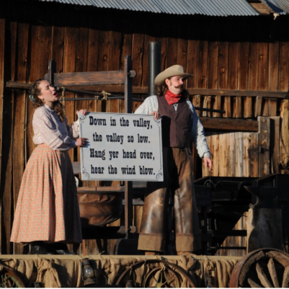 """Photo of two performers in Western style setting and dress, holding a sign with song lyrics: """"Down in the valley,/ the valley so low./ Hang your head over,/ hear the wind blow."""""""