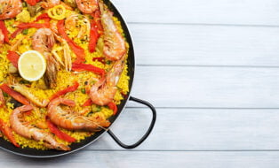 From above paella dish in a pot containing rice and vegetables with seafood.