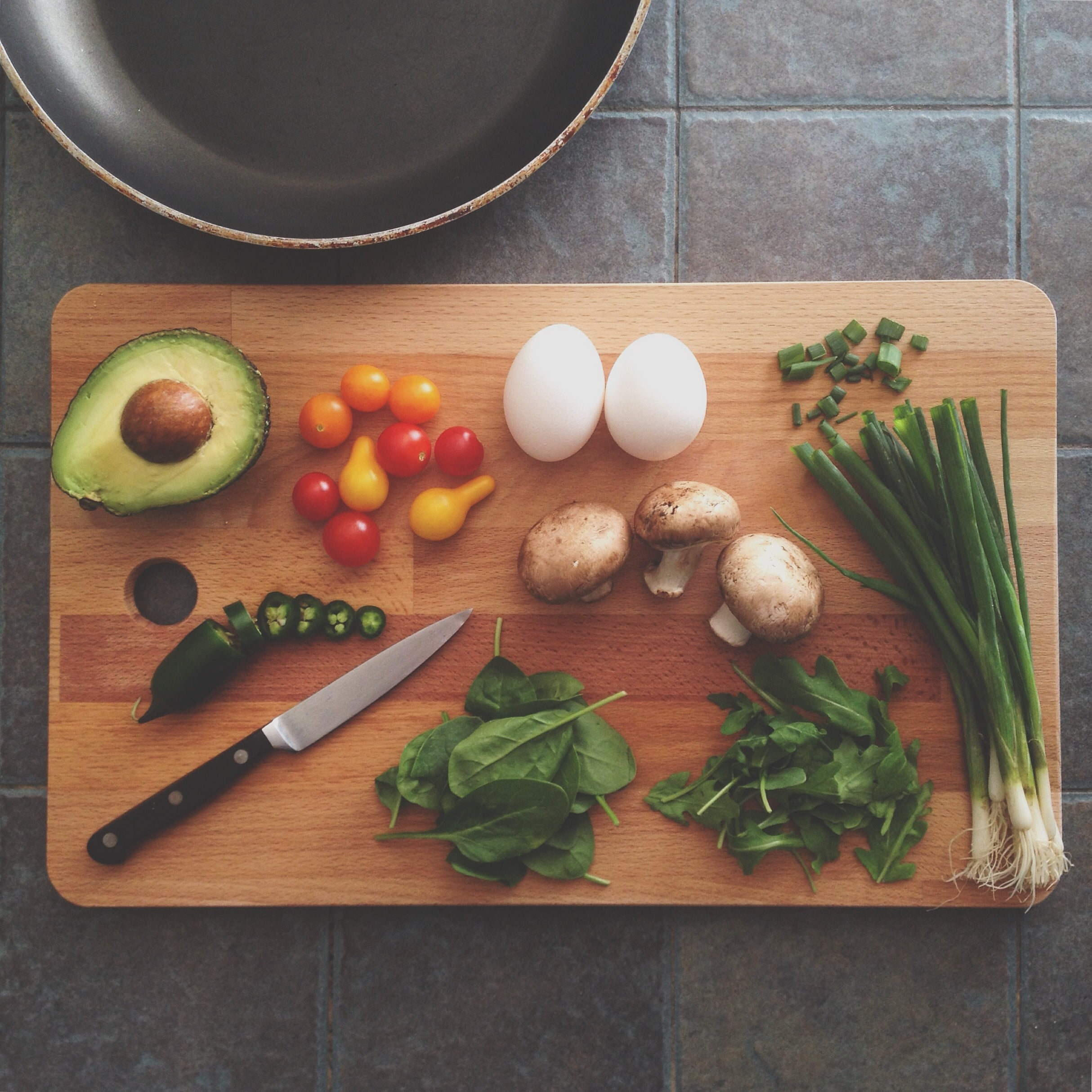 cutting board with green onions, mushrooms, eggs, tomatoes and an avocado