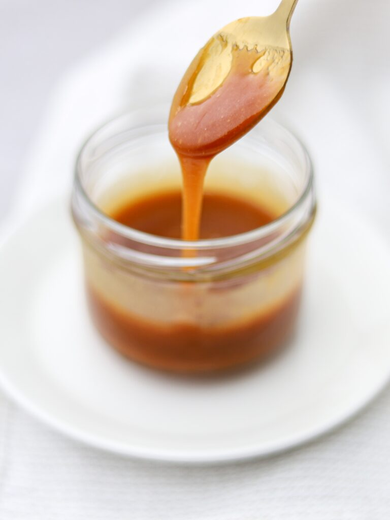 Spoonful of caramel dripping into a jar of caramel