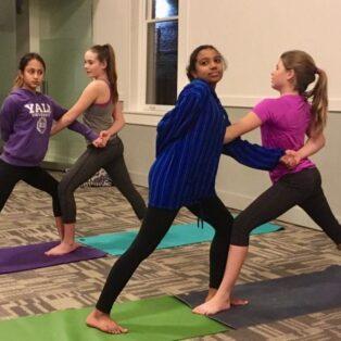 teen girls doing partner yoga