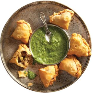 Plate of 6 samosas with potato and pea filling. Bowl of green Cilantro-Mint Chutney for dipping.