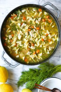 Pot of chicken noodle soup with orange carrots and dill