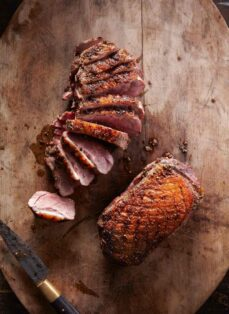 Sliced duck breast and whole duck breast on cutting board