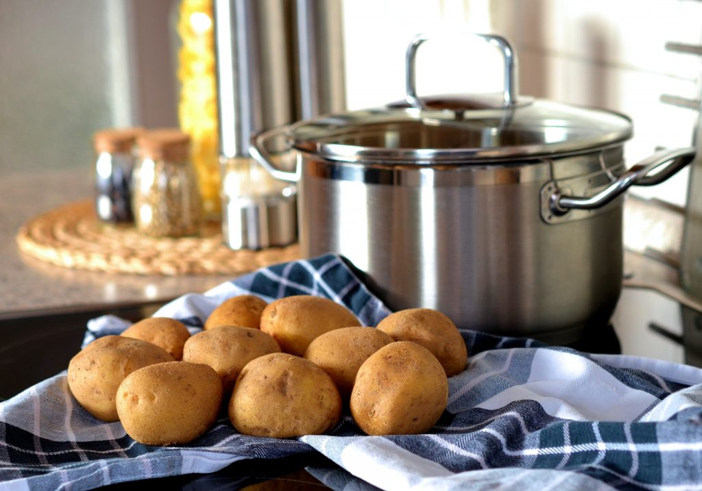 Potatoes on blue and white cloth in front of silver pot