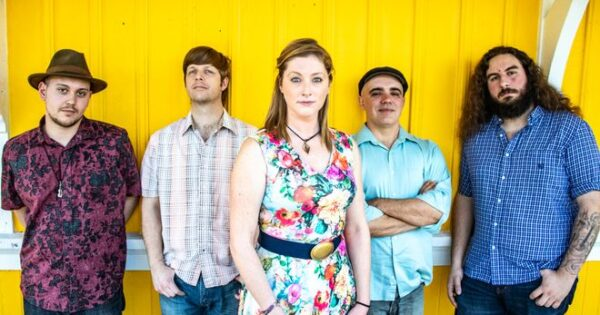 Five band members stand against a yellow background.