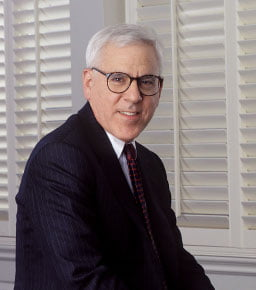 Image of David Rubenstein seated on desk in front of white shutters
